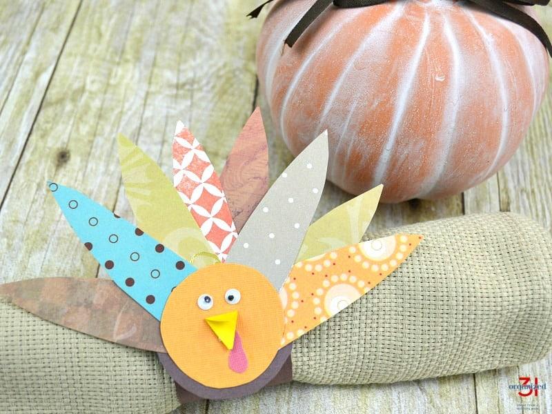 DIY paper turkey napkin ring on tan napkin with terra cotta pumpkin in the background