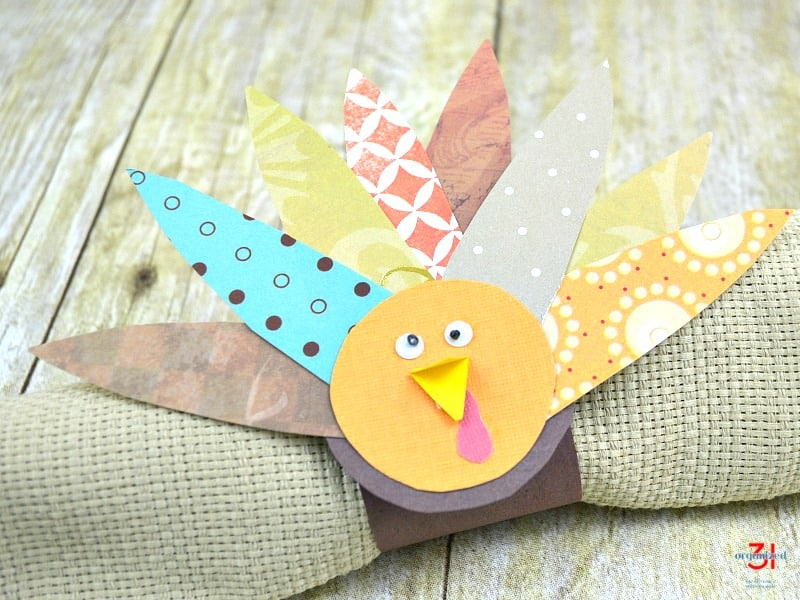 DIY paper craft turkey napkin ring on tan napkin on wood table