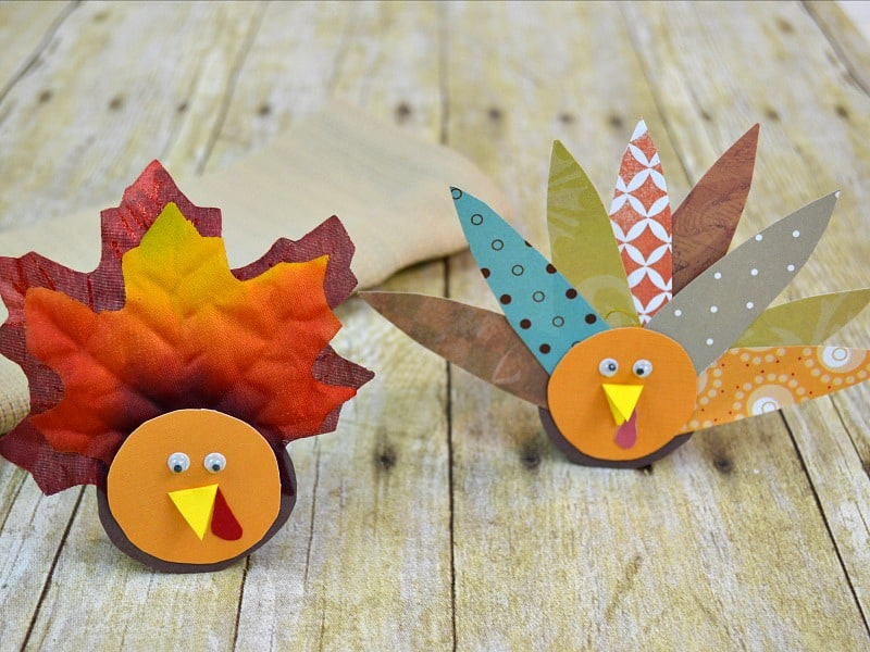 2 different styles of paper craft turkey napkin rings on wood table
