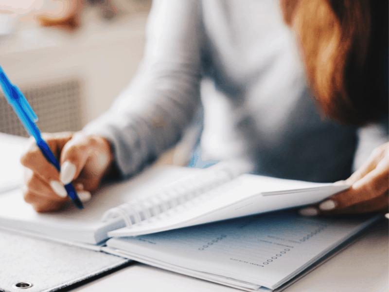 a woman writing in a desk calendar