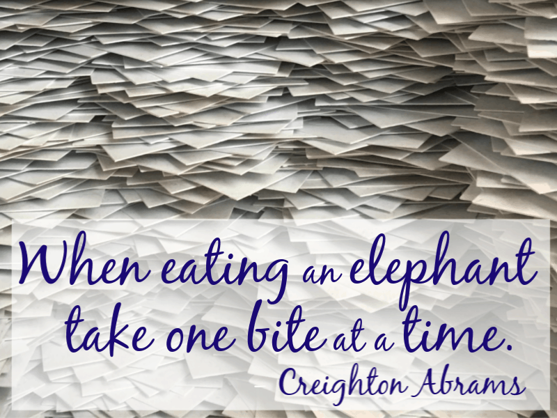 Pile of white sheets of paper with quote overlay reading When eating an elephant take one bite at a time Creighton Abrams