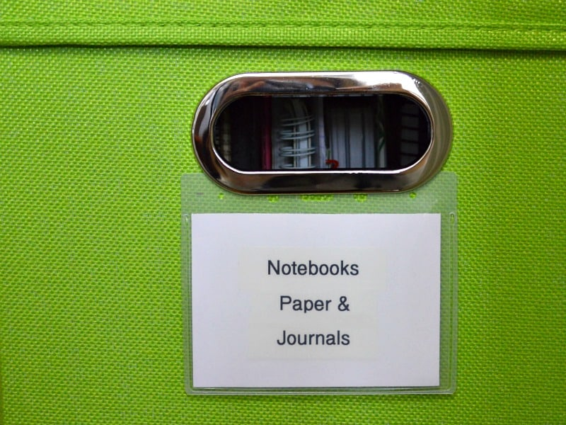 "close-up of label ""notebooks, paper & journals"" on green fabric storage bin"