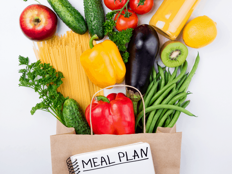 "brown shopping bag with vegetables and pasta falling out of it with notebook with ""meal plan"" written on it"