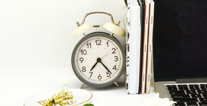 Close up of old-fashioned alarm clock, books and laptop