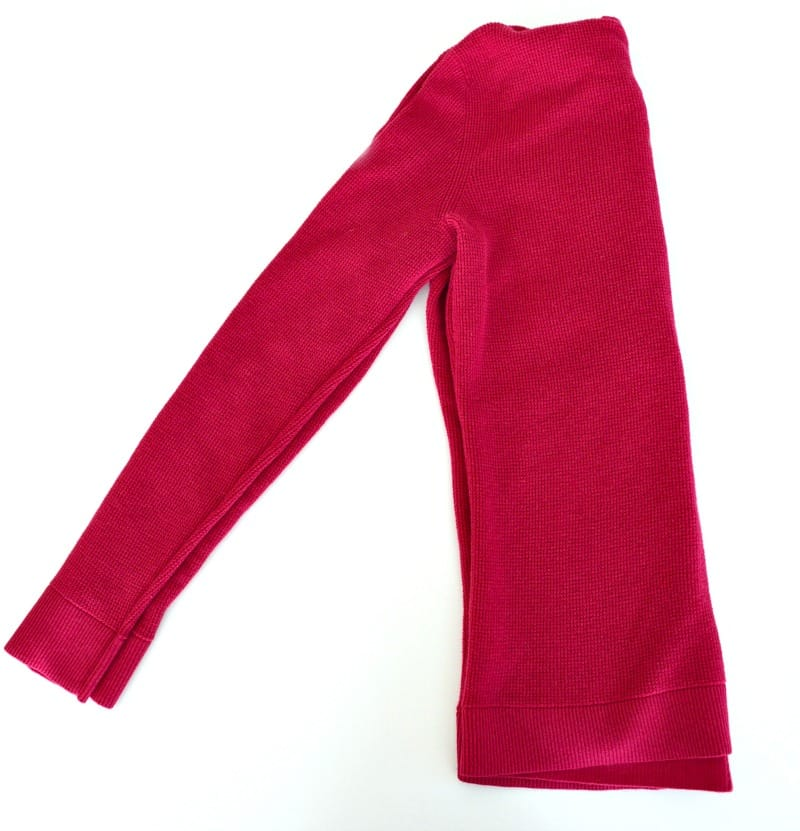 Pink hoodie sweatshirt folded in half with sleeves together.