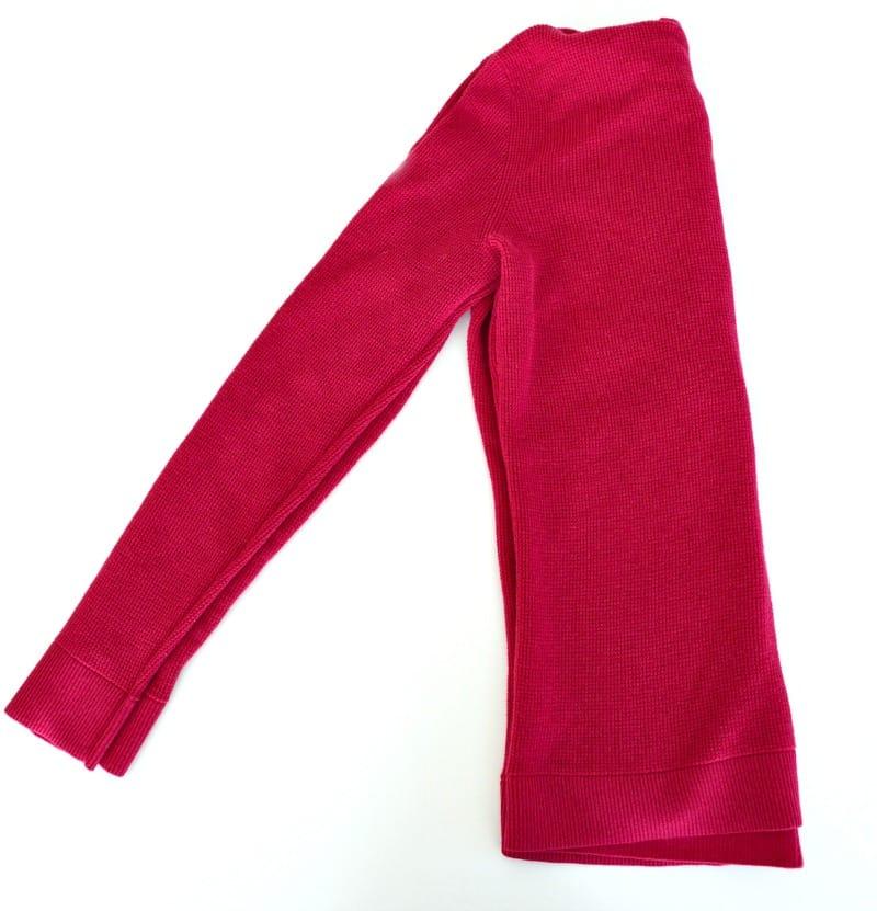 Pink hoodie sweatshirt folded in half with sleeves together.