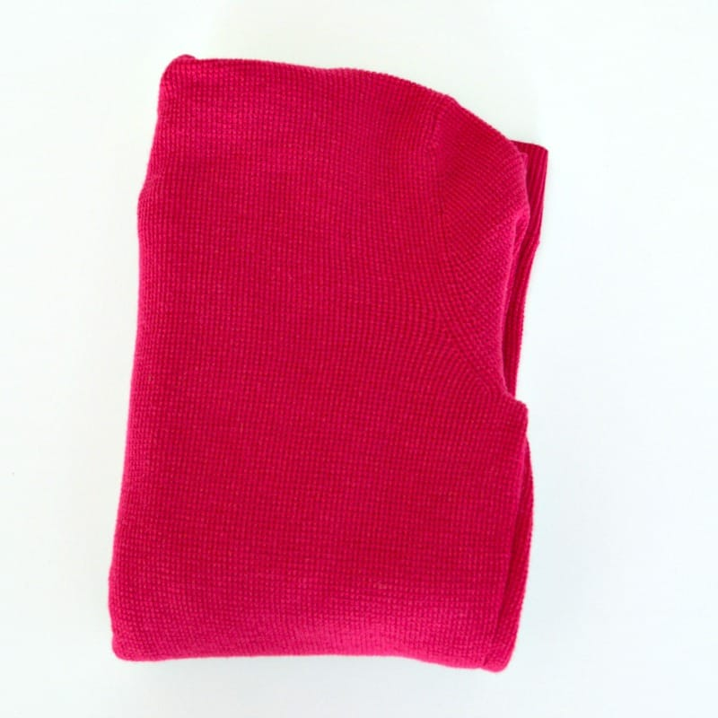 Pink hoodie folded neatly into a square.