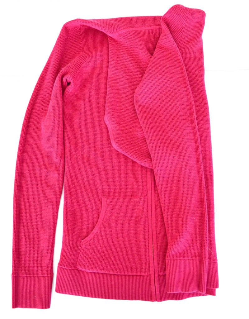 Pink hoodie with the right side folded in neatly onto the body of the hoodie.