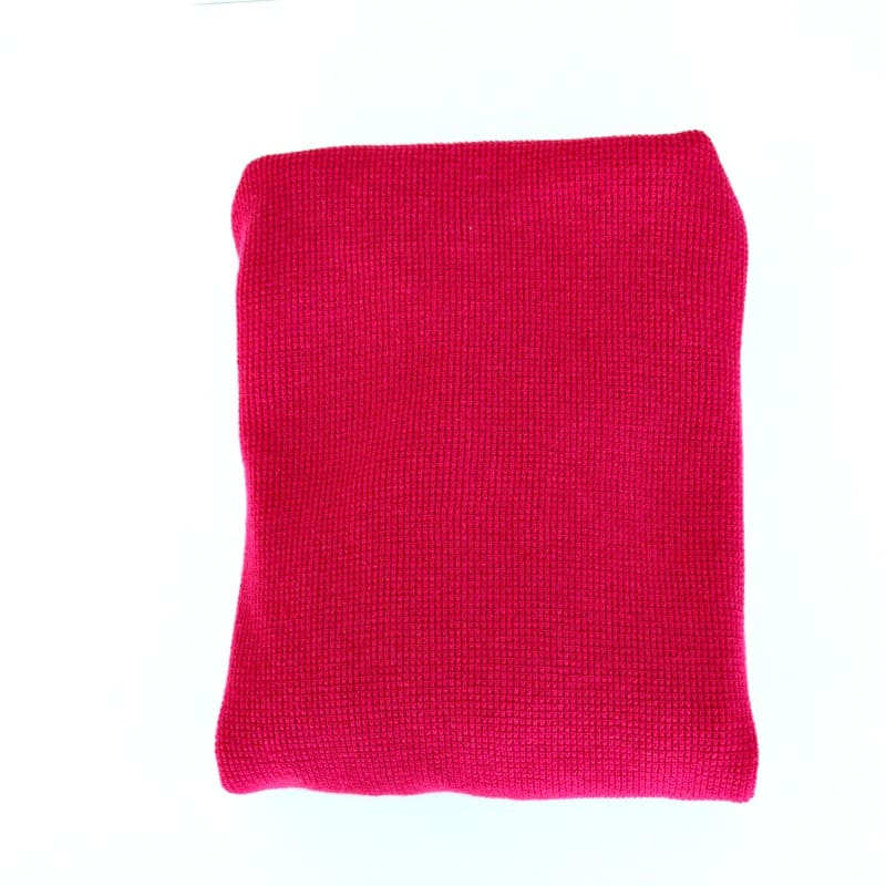 Pink sweatshirt folded into a neat square.