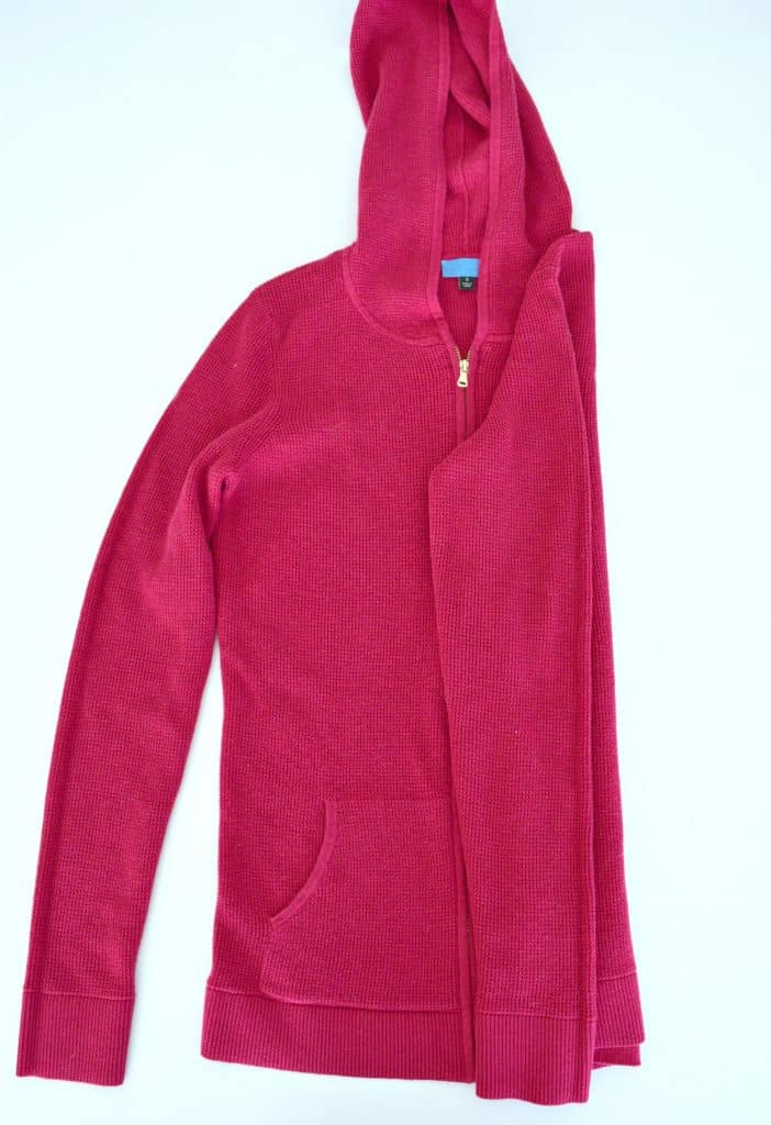 Pink hoodie with the hood up and right side and sleeve folded neatly into the middle.