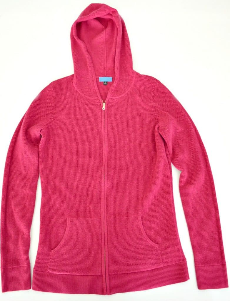 Pink hoodie laid out neatly on a white background.