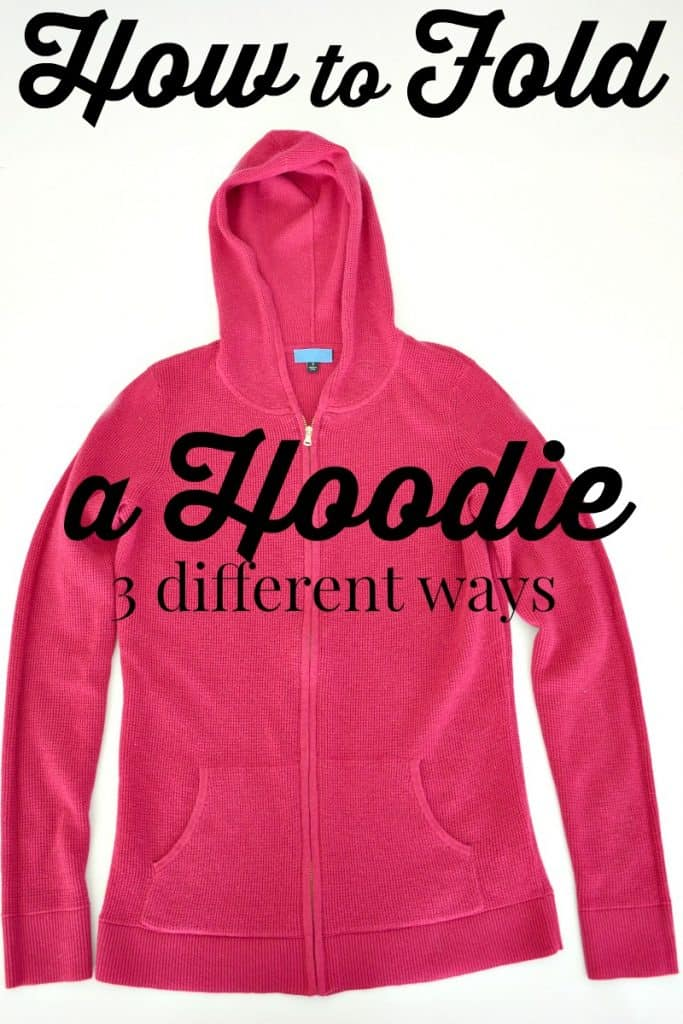 Pink hoodie spread out neatly on a white background with black text overlay reading How to Fold a Hoodie 3 different ways.