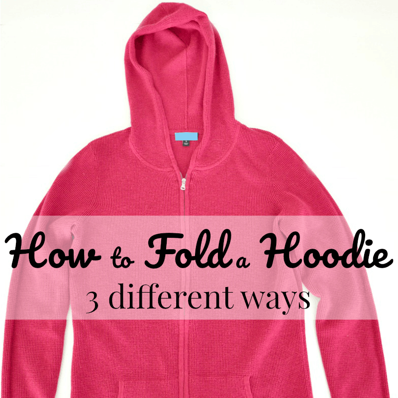 Pink hoodie spread out on white table with text overlay reading How to Fold a Hoodie 3 different ways