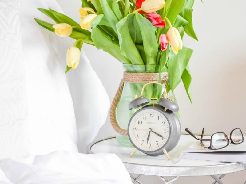 Grey alarm clock on bedside table with eyeglasses and a vase of flowers.