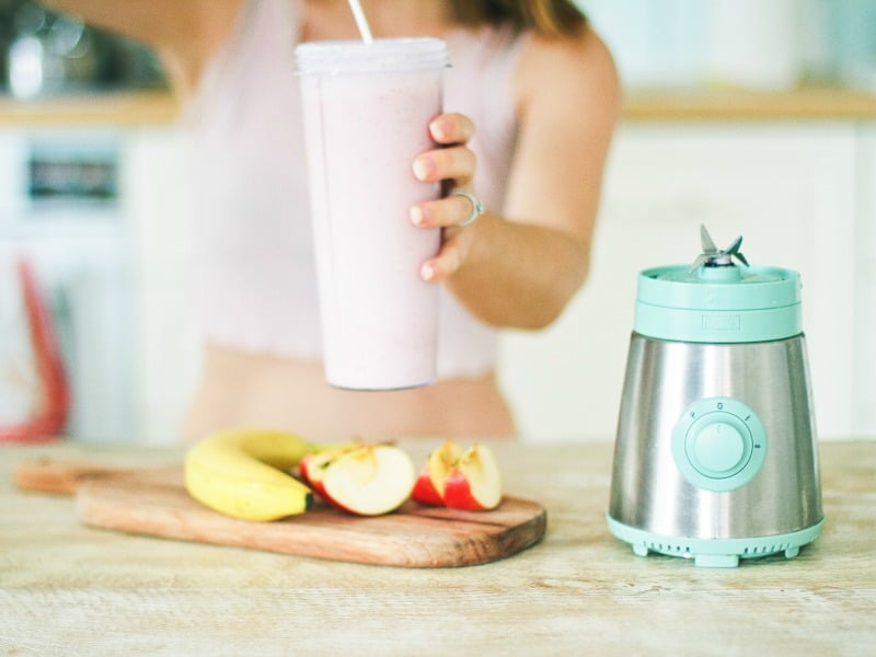 Woman holding glass with smoothie and straw. Fruit on cutting board and blender base on wood counter.