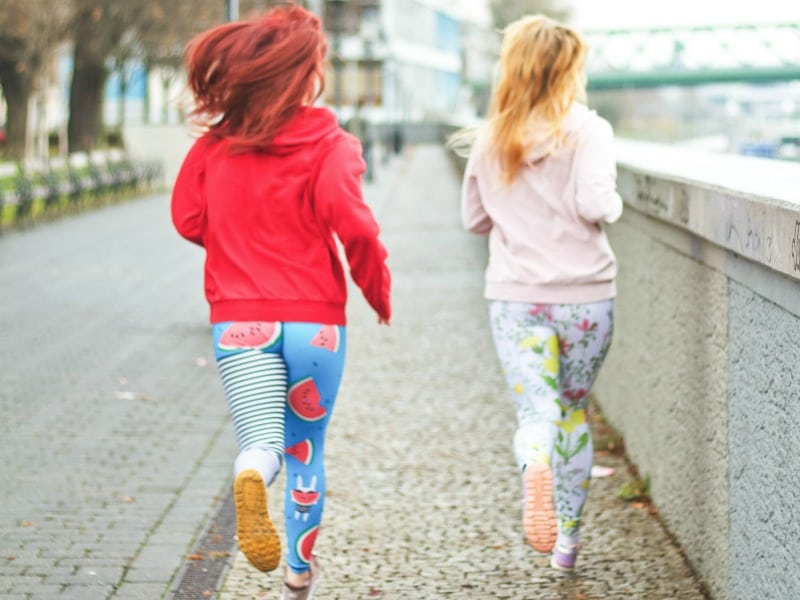 Two women in brightly-colored clothes running next to a wall on a paved sidewalk.