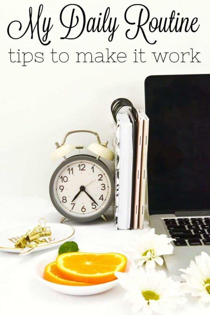 Old-fashioned alarm clock with open laptop, office supplies, white flowers and a dish of orange slices, with black text overlay reading My Daily Routine tips to make it work