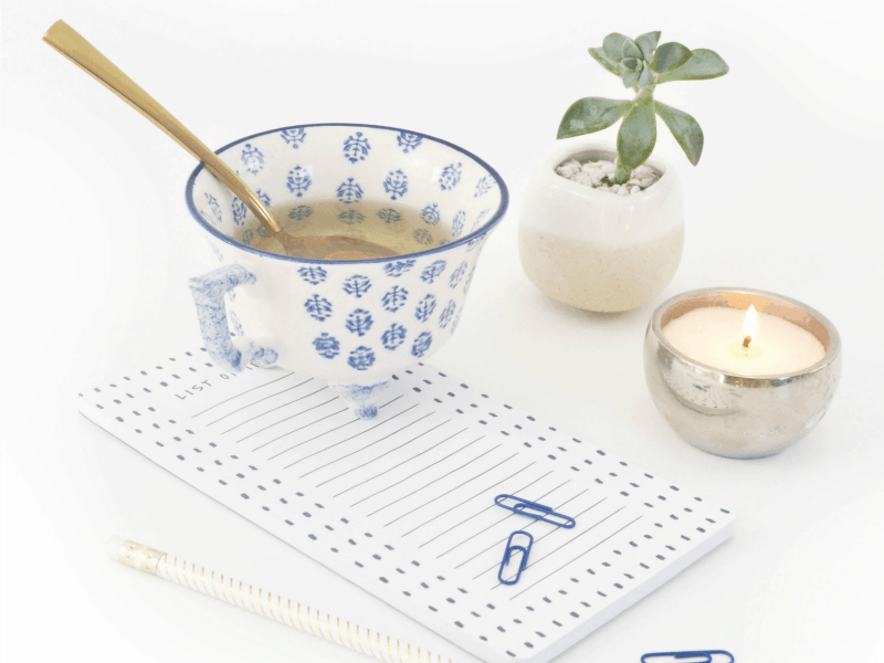White and blue tea cup with gold spoon in the cup. Candle in silver holder, small plant and blue paperclips scattered