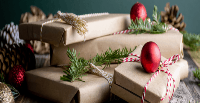 stack of gifts wrapped in brown paper with twine, greenery and red ornament embellishments