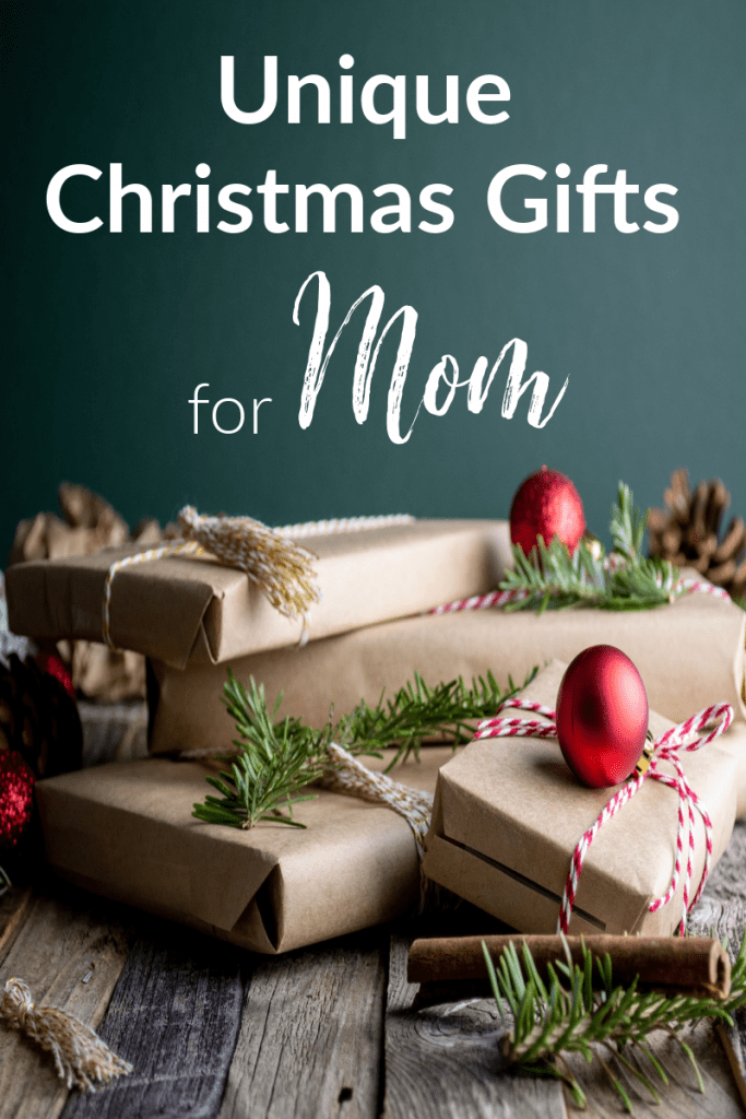 stack of gifts wrapped in brown paper with twine, greenery and red ornament embellishments  with title text reading Unique Christmas Gifts for Mom