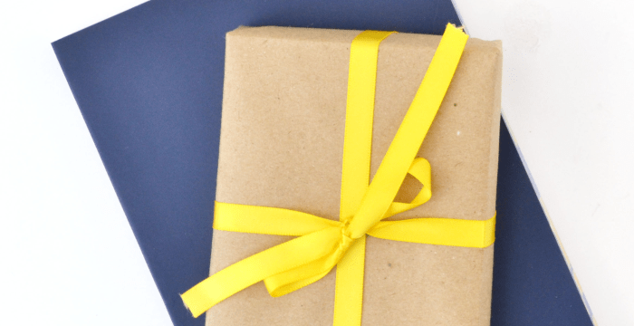 gift wrapped in brown paper with yellow ribbon stacked on navy blue gift box