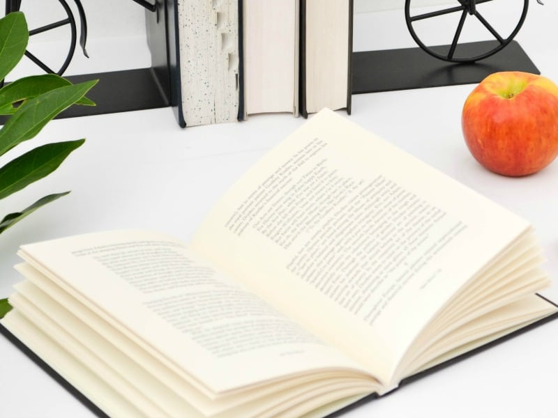 open book with red apple and books in bookends behind