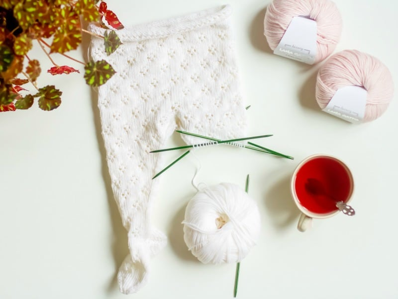 pink and white balls of yarn, with knitted project, cup of tea and plant