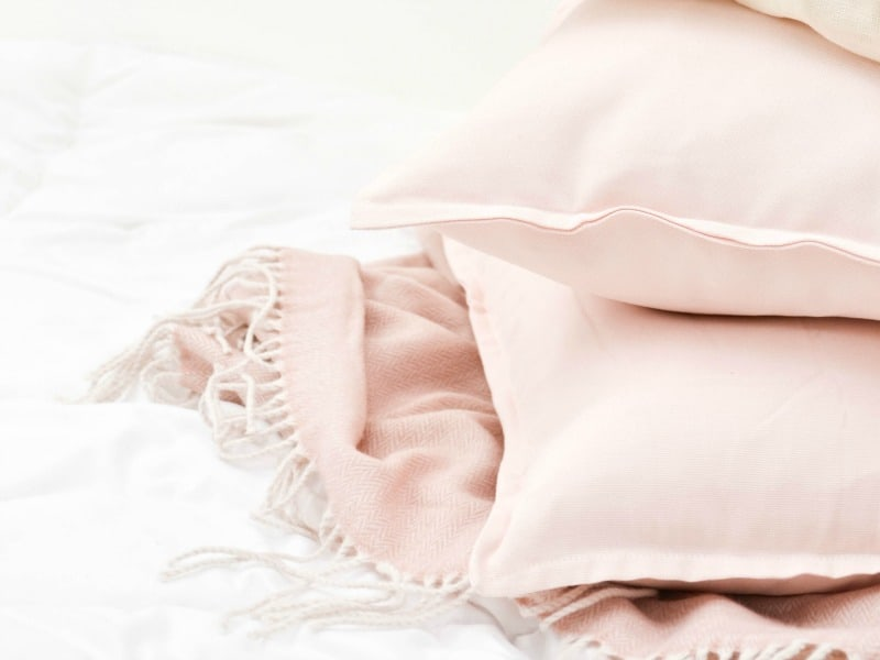 pile of pink pillows and pink blanket on a white bed