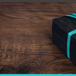 black box with turquoise ribbon on dark brown table with blue box overlay