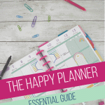 happy planner calendar with paper clips and pens on white wood table