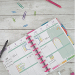 happy planner calendar with paper clips and pens and pink box overlay on bottom