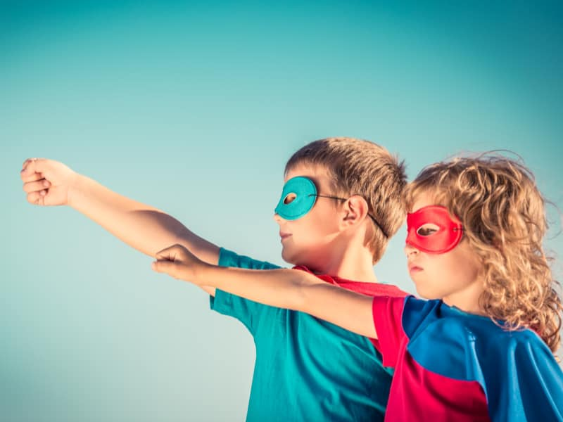 two young children in superhero masks and capes each with arm out in front of them