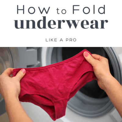 woman's hands holding up underwear in front of open clothes dryer