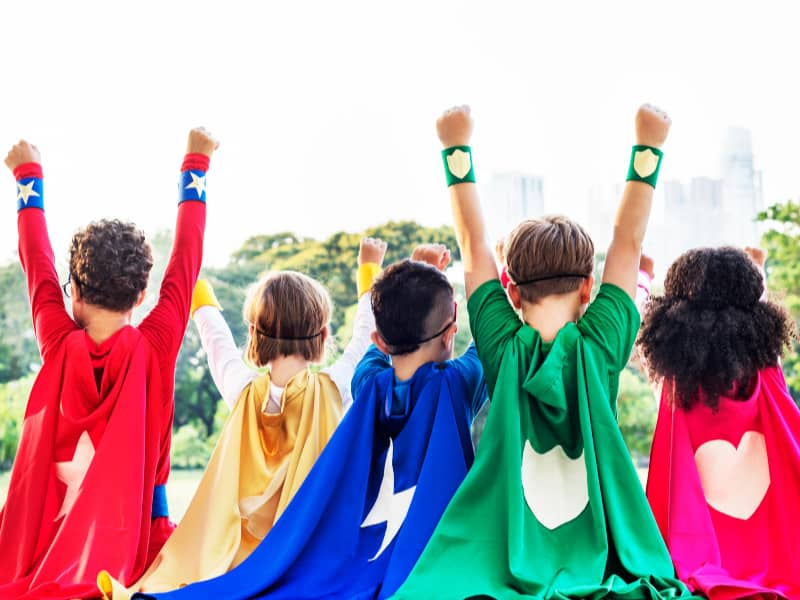 five kids wearing colored super hero capes with their arms up in the air