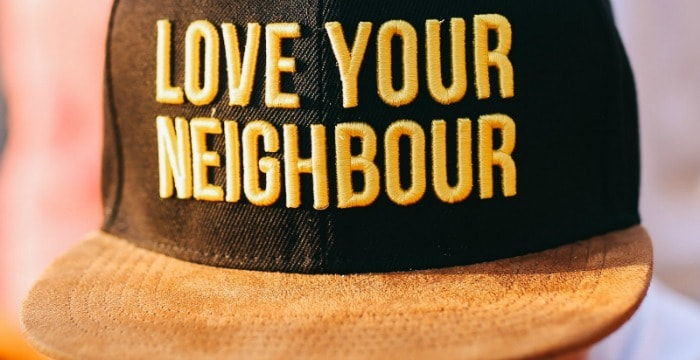 "brown baseball hat with gold ""Love Your Neighbor"""