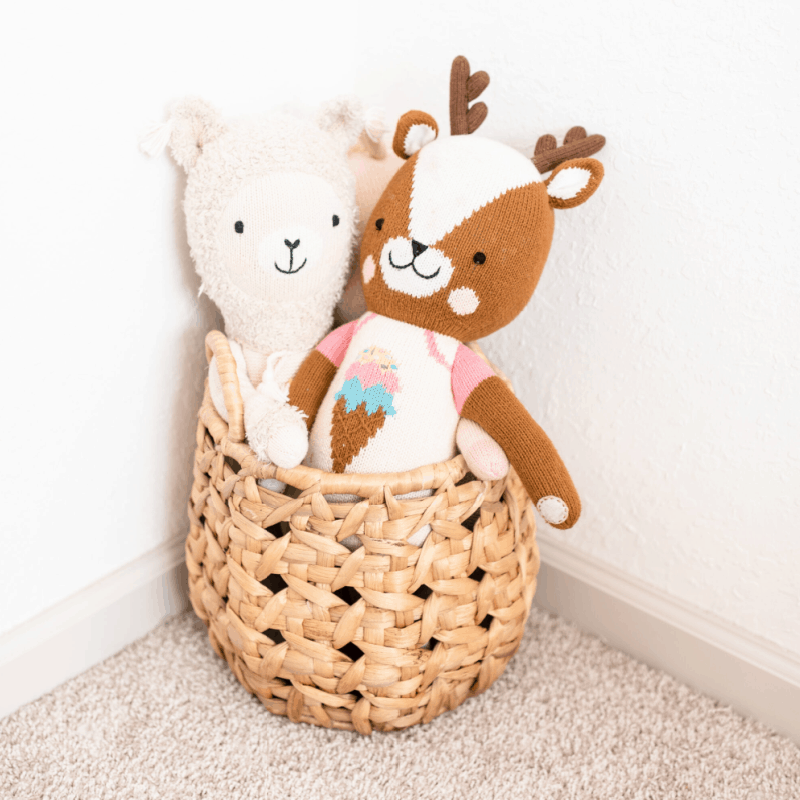 2 stuffed animals in a basket in a room corner
