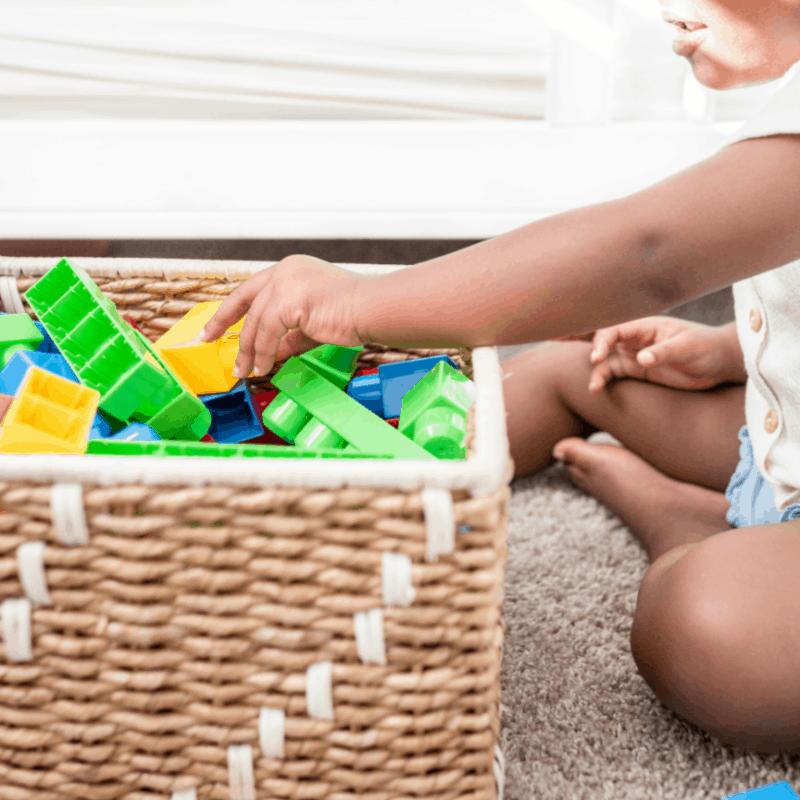 child putting blocks way in basket