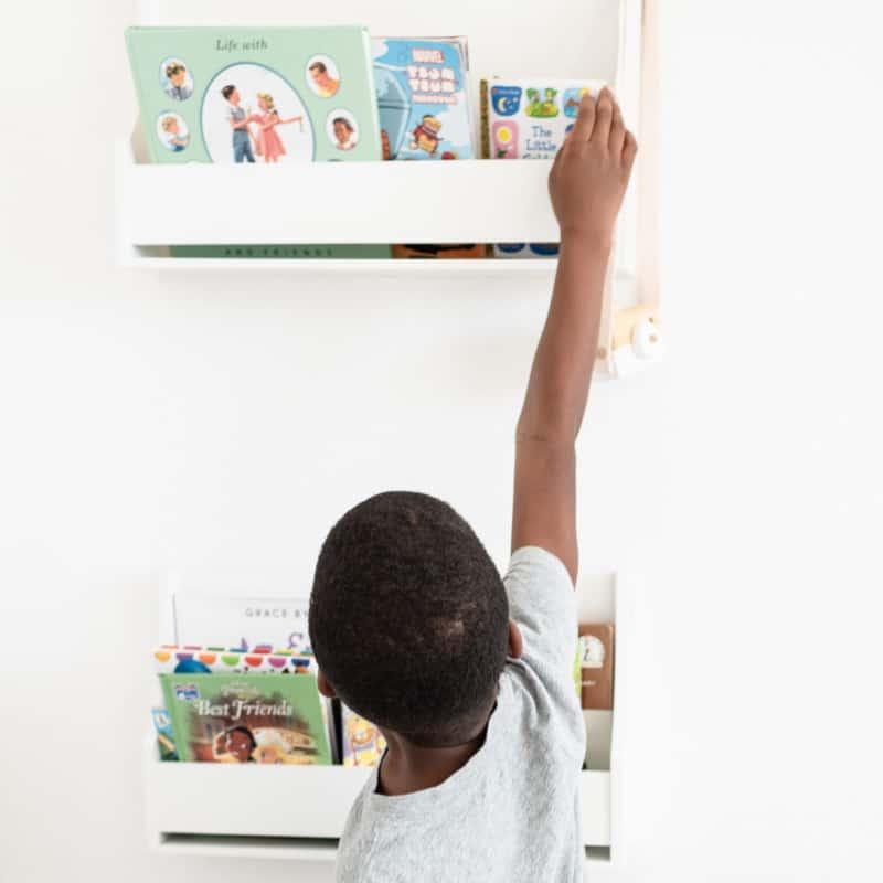 boy reaching for book in wall book shelf