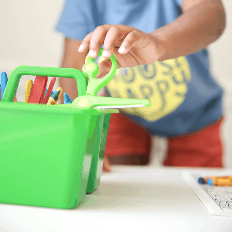 close up of child's hand putting art supplies away in bright green caddy