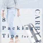 woman pulling white carry on suitcase