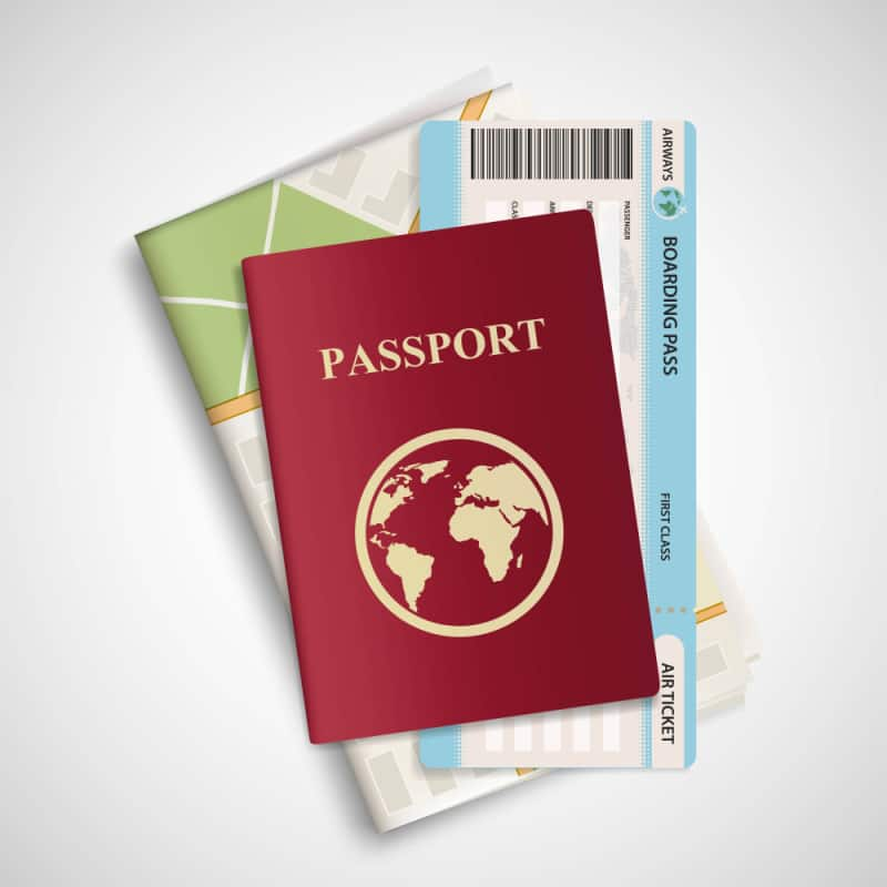passport on top of stack of maps on white table