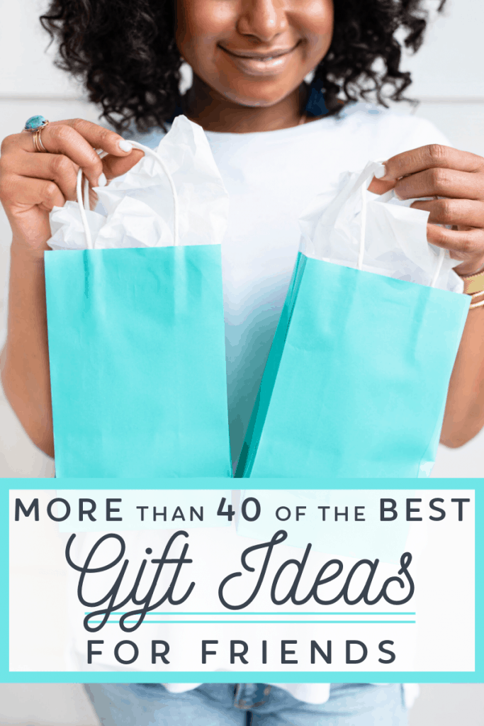 woman in white shirt holding 2 blue gift bags with title text overlay reading More Than 40 Of The Best Gift Ideas For Friends