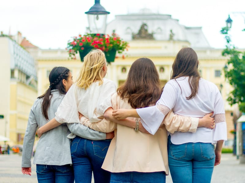 back view of 4 women with arms around each other's backs