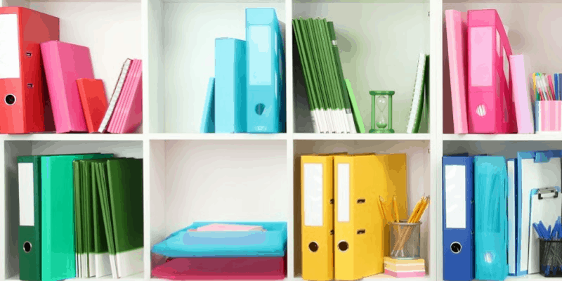 books and binders organized by color on white shelves