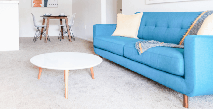 tidy living room with blue couch and white round coffee table