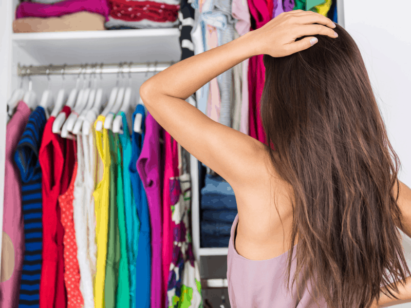 woman with hand on head looking into closet of clothes