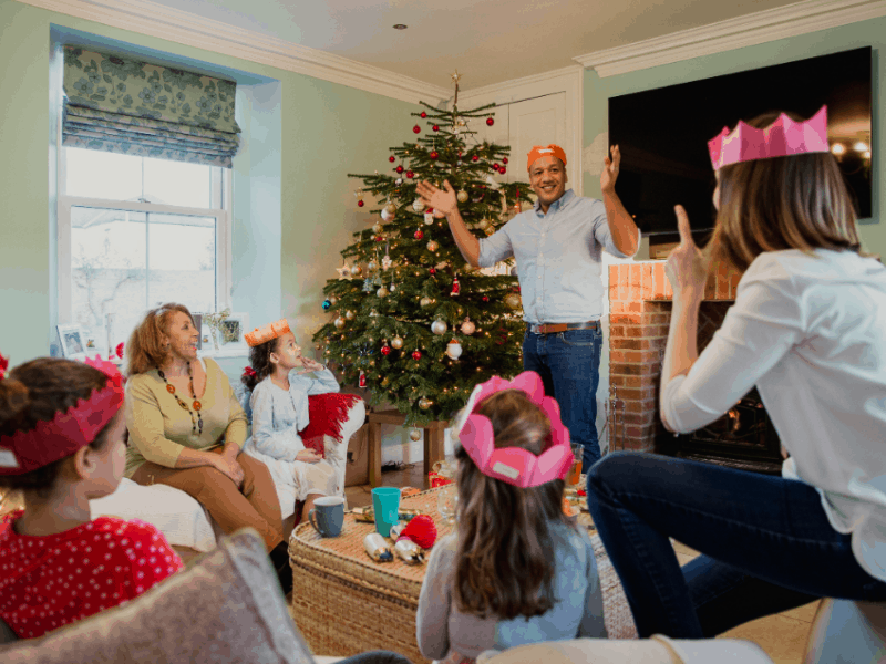 large family playing game by Christmas tree