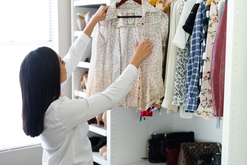 woman holding blouse on hanger in neatly organized closet
