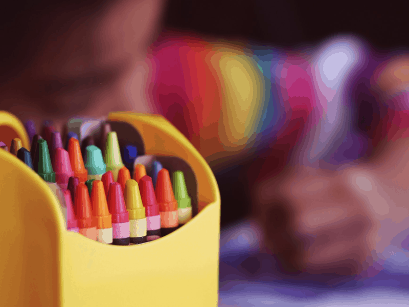 close up of box of crayons with child coloring in the background