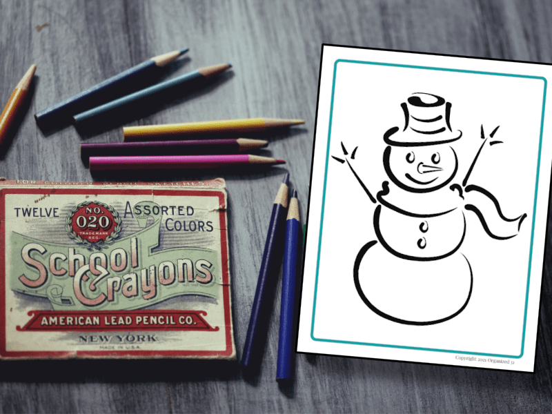 snowman coloring sheet on table with box of crayons on wood table